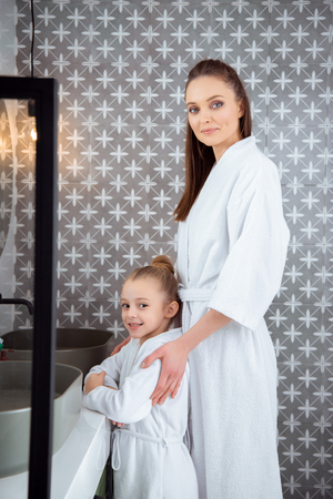 happy mother standing with daughter in bath robes