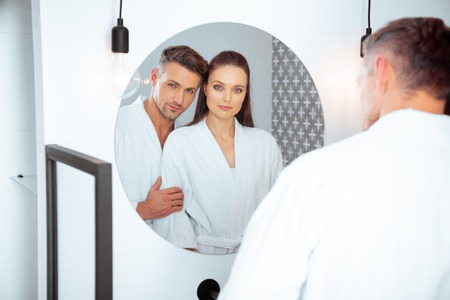 handsome husband hugging attractive wife in bathroom while looking at mirror Banco de Imagens