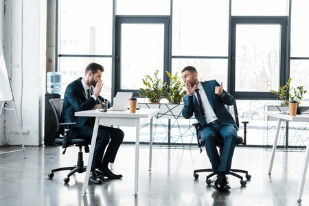 businessmen in formal wear gossiping while sitting in modern office