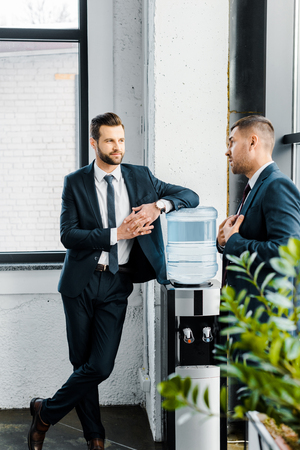 businessman standing with crossed legs and  talking with coworker in modern office