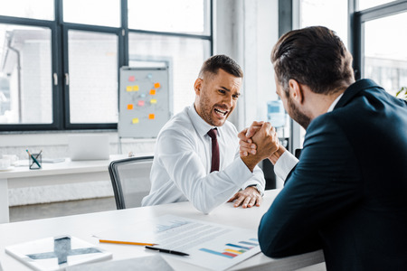 handsome businessman competing arm wrestling with coworker in modern office Stock Photo