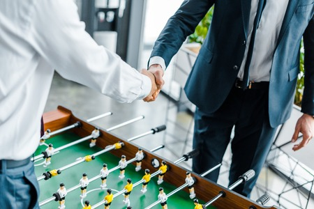 cropped view of businessmen shaking hands near table football Stok Fotoğraf