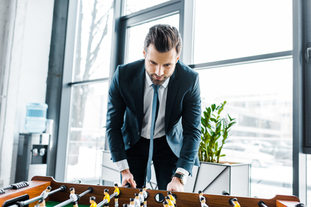 bearded businessman in formal wear playing table football