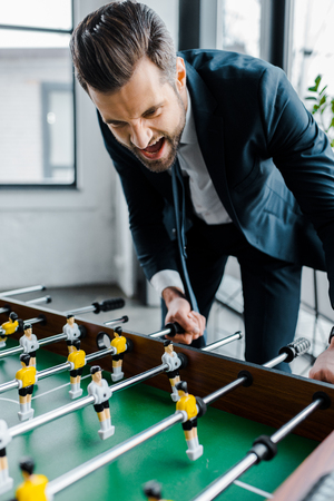 happy bearded businessman in formal wear playing table football