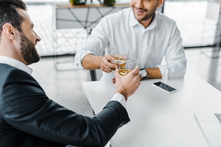 bearded businessman toasting with whiskey while sitting in modern office with coworker