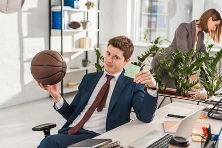 selective focus of businessman holding sticky note with later lettering with basketball in hand with coworker on background, procrastination concept
