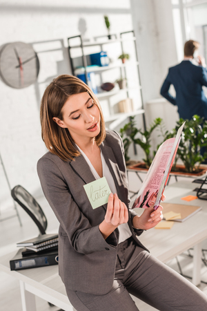 selective focus of businesswoman holding sticky note with later lettering and reading magazine with coworker on background, procrastination concept