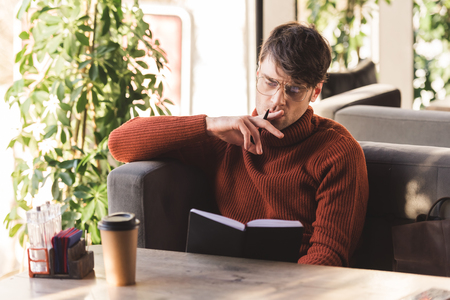 thoughtful man in glasses holding pen while looking at notebook near disposable cup in cafe Imagens
