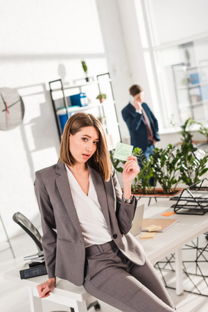 selective focus of businesswoman holding sticky note with later lettering with coworker on background, procrastination concept Stock Photo