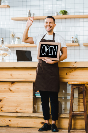 handsome cashier standing near wooden bar counter, holding chalkboard with open lettering and greeting in coffee house Banco de Imagens