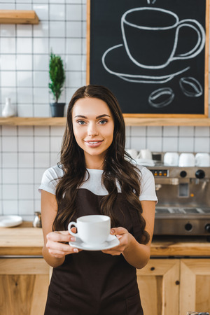 attractive barista in brown apron holding cup and saucer in coffee house