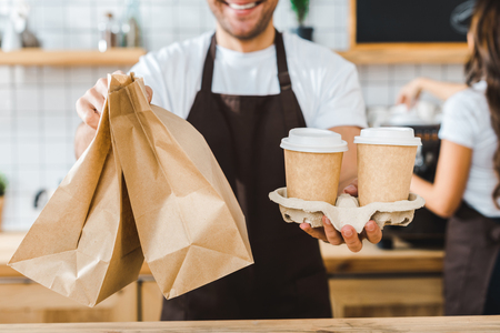 cropped view of cashier holding paper cups and bags wile brunette barista making coffee in coffee house Banco de Imagens