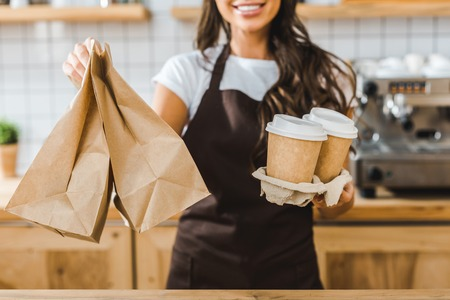 cropped view of brunette cashier holding paper cups and bags in coffee house