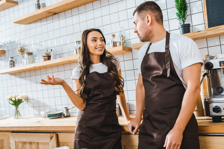 cashiers in aprons talking near wooden bar counter in coffee house Banque d'images - 118416448