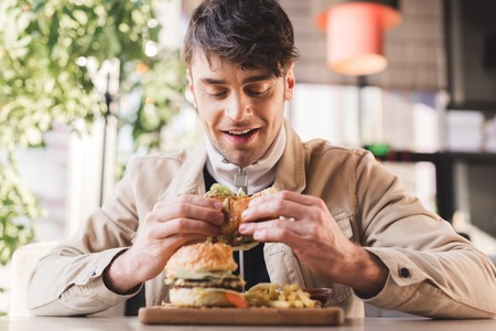 selective focus of happy young man looking at tasty burger near french fries on cutting board in cafe Stock Photo