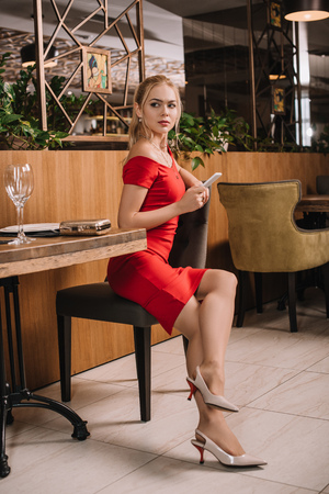 attractive woman in red dress sitting in restaurant and waiting for man