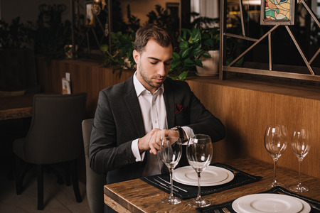 handsome man in suit waiting for girlfriend in restaurant and looking at watch