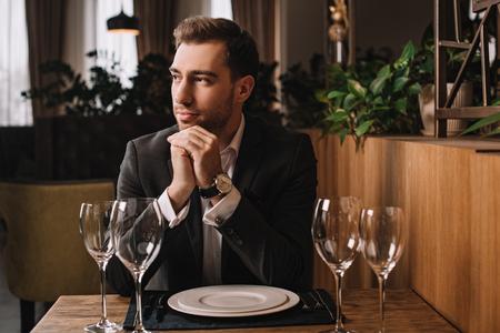 handsome man in suit waiting for girlfriend in restaurant 写真素材