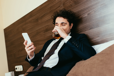 adult businessman using smartphone and drinking whiskey on bed in hotel room Reklamní fotografie