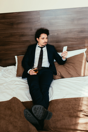 adult businessman using smartphone and holding glass of cognac on bed in hotel room Reklamní fotografie
