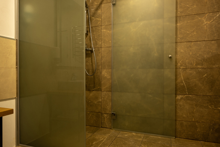 bathroom interior with brown tile and glass shower cabin Фото со стока
