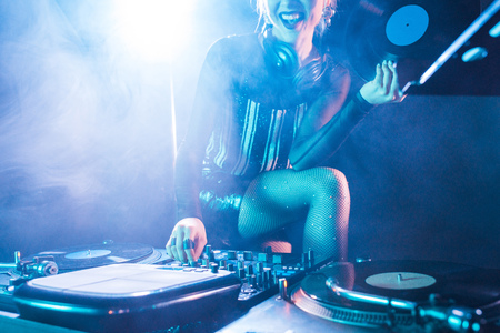 cropped view of cheerful dj woman holding retro vinyl record and standing near dj equipment in nightclub with smoke