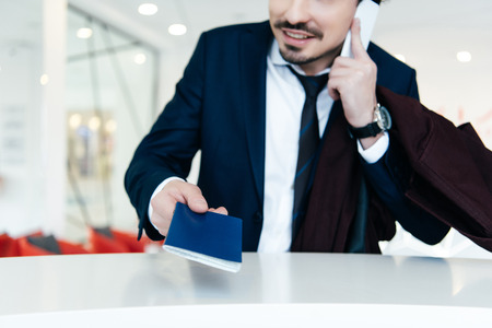 cropped view of businessman in suit with passport talking on smartphone while making check-in at the hotel