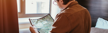 back view of man in eyeglasses looking at map in hotel room Imagens