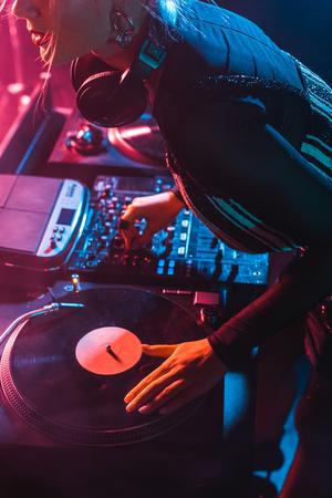 cropped view of focused dj woman using dj equipment in nightclub Reklamní fotografie