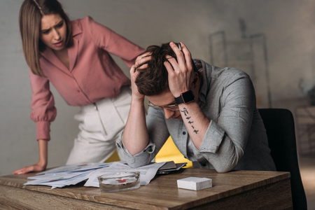 attractive woman looking at man holding head while having headache