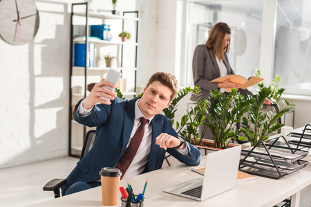 selective focus of handsome man taking selfie with female coworker on background Stock Photo