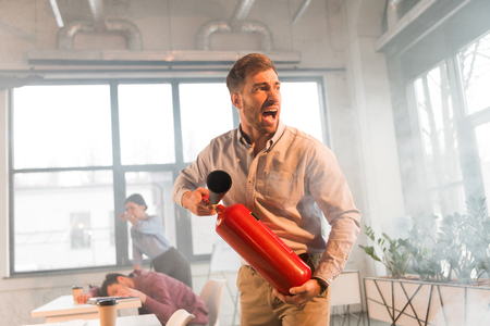 frightened businessman holding extinguisher and screaming in office with smoke near coworkers