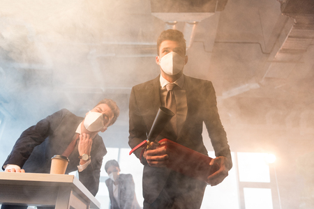 businessman in mask holding extinguisher near coworkers in office with smoke 스톡 콘텐츠