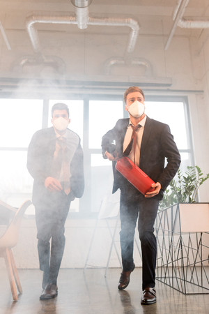 businessman in mask holding extinguisher near colleague while walking in office with smoke