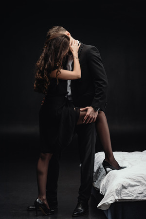 passionate young couple in formal wear kissing and embracing isolated on black Фото со стока