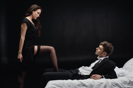 handsome man lying on bed and looking at beautiful woman in stockings isolated on black