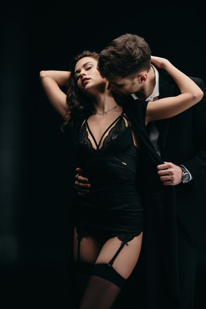 uomo che bacia e abbraccia bella donna in lingerie isolata su black