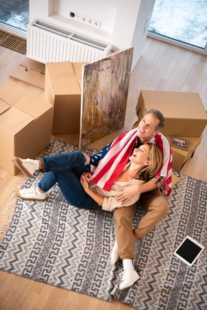 happy smiling couple sitting on fleece blanket on floor at new home