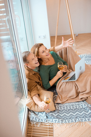 excited couple looking up while sitting on floor at new home and using laptop