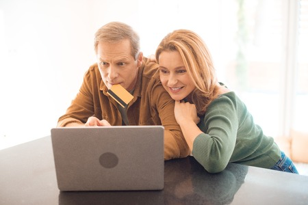 concentrated man holding credit card with lips while using laptop together with wife