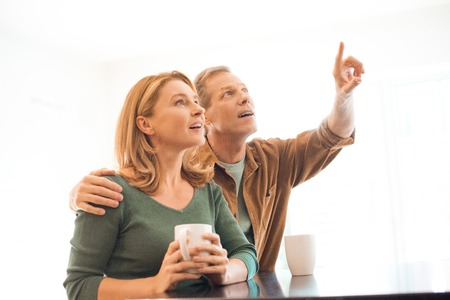 man pointing with finger while hugging wife with coffee cup in hands Stock fotó