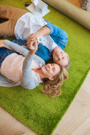 selective focus of woman holding keys with house model trinket while lying on green carpet with smiling husband