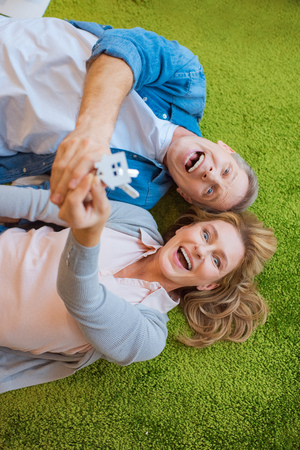 selective focus of excited couple holding keys with house model trinket while lying on green carpet
