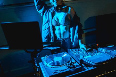 cropped view of smiling dj woman standing near dj mixer Reklamní fotografie