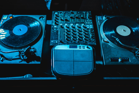 dj mixer with equalizer and vinyl records in nightclub