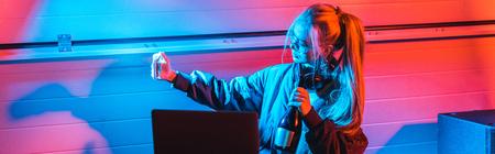 Attraktive blonde Frau, die Flasche hält und Selfie auf dem Smartphone macht
