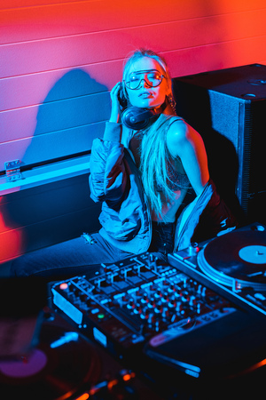 dj woman listening music in headphones while sitting with closed eyes