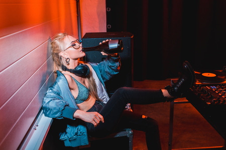 attractive dj girl drinking from bottle while sitting in nightclub