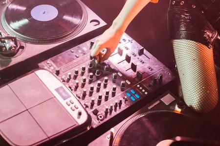 cropped view of dj girl touching dj equipment in nightclub
