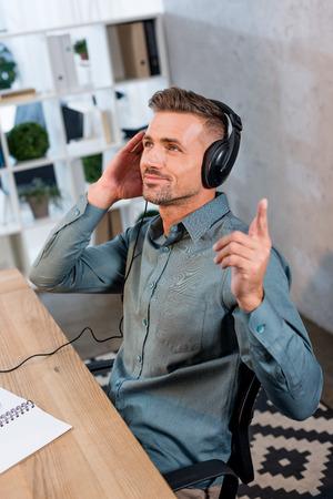 happy businessman listening music in headphones in modern office